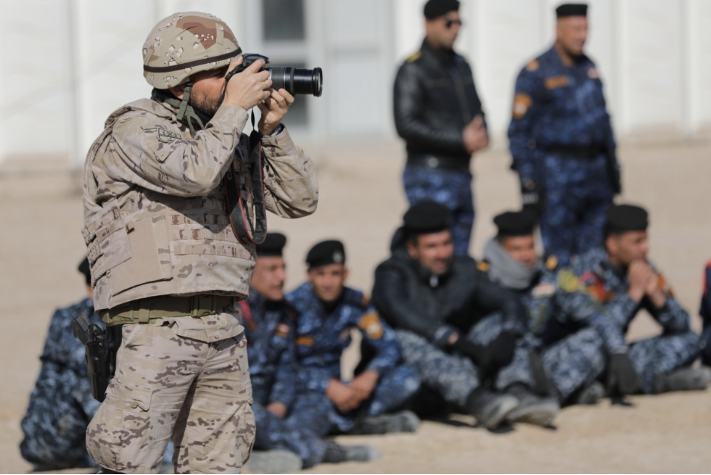 A CJTF-OIR trainers takes an image of Iraqi Police Force training to build greater security in liberated areas